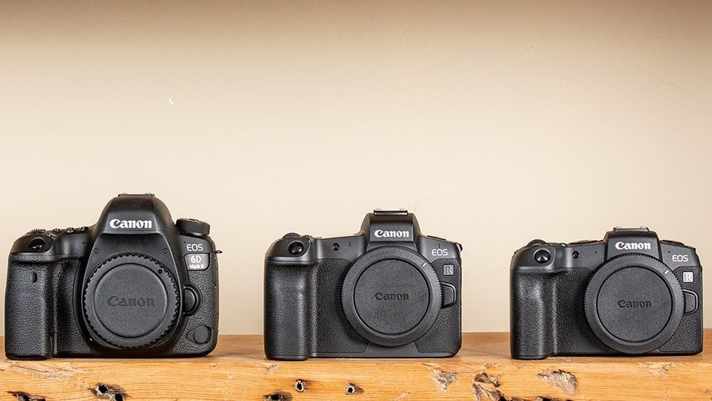Full frame cameras in a row on wood